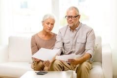 Ältere Paare mit Papieren und Taschenrechner zu Hause Lizenzfreie Stockfotos