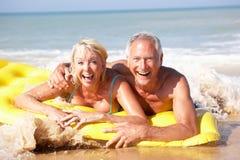 Ältere Paare am Strandfeiertag Lizenzfreie Stockfotos
