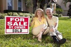 Ältere Paare und Haus für Verkauf verkauften Zeichen Lizenzfreie Stockfotografie