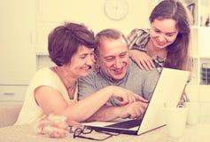 Ältere Paare und Tochter mit Laptop zu Hause Stockfotografie