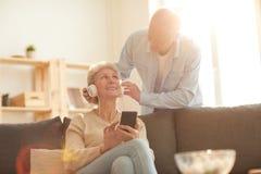 Ältere Paare unter Verwendung der Geräte stockfotos