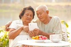 Ältere Paare unter Verwendung der Tablette Stockfotografie
