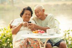 Ältere Paare unter Verwendung des Handys Stockbild