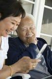 Ältere Paare unter Verwendung des Handys, der draußen lächelt Stockbild