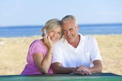 Ältere Paare unter Verwendung des Handys am Tisch durch Beach Lizenzfreies Stockfoto