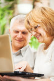 Ältere Paare unter Verwendung des Laptops Stockfotos