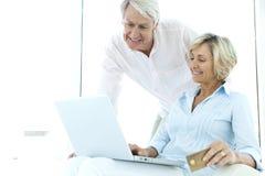 Ältere Paare unter Verwendung des Laptops lizenzfreie stockbilder