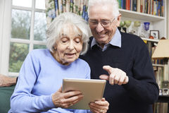 Ältere Paare unter Verwendung Digital-Tablets zu Hause Stockbilder