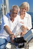 Ältere Paare unter Verwendung SatNav GPS auf einem Segel-Boot Stockfoto