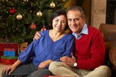 Ältere Paare vor Weihnachtsbaum Lizenzfreies Stockfoto