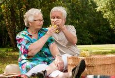 Ältere Paare, welche die Trauben teilen Stockfoto
