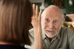 Ältere Paare zu Hause, die auf verärgerten Mann sich konzentrieren stockfotografie