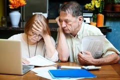 Ältere Paare zu Hause mit vielen Rechnungen Lizenzfreie Stockfotos