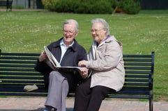 Ältere Paarlesezeitung auf einer Parkbank Lizenzfreies Stockfoto