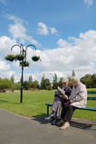 Ältere Paarlesezeitung auf einer Parkbank Lizenzfreies Stockbild
