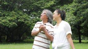 Ältere Paarleute, die im Frühjahr Tag in der Natur genießen und auf Picknick mit glücklichem Gefühl gehen stock footage