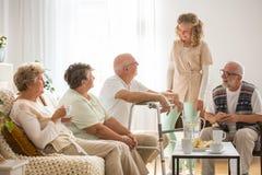 Ältere Patienten mit hilfreicher junger Krankenschwester am Pflegeheim lizenzfreie stockbilder