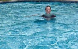 Ältere pensionierte Mannschwimmen im Pool lizenzfreies stockbild