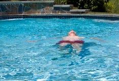Ältere pensionierte Mannschwimmen im Pool stockfotografie