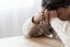 Ältere Person in der Melancholie betend mit Rosenbeet lizenzfreie stockbilder