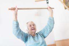 Ältere Personen 96 Jahre alte Frau, die mit einem Stock sitzt auf ihrem Schlechten trainieren stockfotos