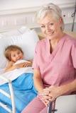 Ältere Personen warten in der USA-Kinderheilkunde mit Kindpatienten Lizenzfreie Stockbilder