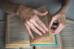Ältere Personenhände mit geöffneten Büchern, Abschluss oben, vorgewählter Fokus, Unschärfe lizenzfreie stockfotografie