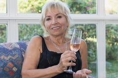 Ältere reife blonde Frau sitzt auf einer Couch Lizenzfreie Stockfotos