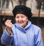 Ältere reife Frau des verschroben Umkippens des Nahaufnahmeporträts, die herauf Faust sich setzt Stockfotografie
