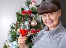 Ältere schöne Frau gegen Weihnachtsbaum Abstraktes Hintergrundmuster der weißen Sterne auf dunkelroter Auslegung Lizenzfreies Stockfoto