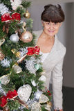 Ältere schöne Frau gegen Weihnachtsbaum Abstraktes Hintergrundmuster der weißen Sterne auf dunkelroter Auslegung Lizenzfreie Stockfotos