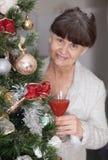 Ältere schöne Frau gegen Weihnachtsbaum Abstraktes Hintergrundmuster der weißen Sterne auf dunkelroter Auslegung Stockfoto