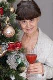 Ältere schöne Frau gegen Weihnachtsbaum Abstraktes Hintergrundmuster der weißen Sterne auf dunkelroter Auslegung Stockfotos