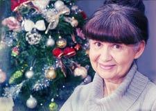 Ältere schöne Frau mit Glas Wein gegen Weihnachtsbaum Abstraktes Hintergrundmuster der weißen Sterne auf dunkelroter Auslegung Lizenzfreies Stockfoto