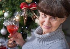 Ältere schöne Frau mit Glas Wein gegen Weihnachtsbaum Abstraktes Hintergrundmuster der weißen Sterne auf dunkelroter Auslegung Stockfoto