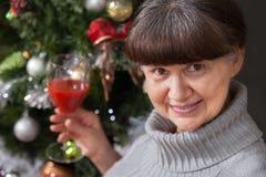 Ältere schöne Frau mit Glas Wein gegen Weihnachtsbaum Abstraktes Hintergrundmuster der weißen Sterne auf dunkelroter Auslegung Stockbild