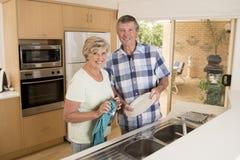 Ältere schöne Mittelalterpaare herum 70 Jahre alte lächelnde glückliche zu Hause Küche, welche die Teller zusammen schauen süß wa Stockfoto