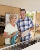 Ältere schöne Mittelalterpaare herum 70 Jahre alte lächelnde glückliche zu Hause Küche, welche die Teller zusammen schauen süß wa Lizenzfreie Stockbilder
