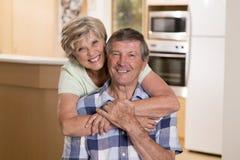 Ältere schöne Mittelalterpaare herum 70 Jahre alte lächelnde glückliche zusammen zu Hause Küche, die im Lebenszeitehemann süß sch Stockfotografie