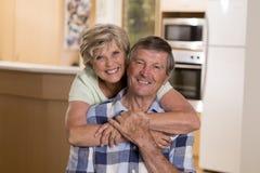 Ältere schöne Mittelalterpaare herum 70 Jahre alte lächelnde glückliche zusammen zu Hause Küche, die im Lebenszeitehemann süß sch Lizenzfreie Stockbilder