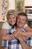 Ältere schöne Mittelalterpaare herum 70 Jahre alte lächelnde glückliche zusammen zu Hause Küche, die im Lebenszeitehemann süß sch Lizenzfreies Stockfoto