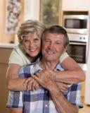 Ältere schöne Mittelalterpaare herum 70 Jahre alte lächelnde glückliche zusammen zu Hause Küche, die im Lebenszeitehemann süß sch Lizenzfreie Stockfotografie
