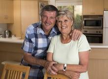 Ältere schöne Mittelalterpaare herum 70 Jahre alte lächelnde glückliche zusammen zu Hause Küche, die im Lebenszeitehemann süß sch Lizenzfreie Stockfotos