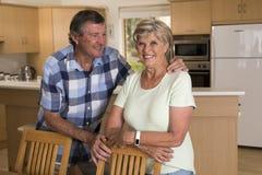 Ältere schöne Mittelalterpaare herum 70 Jahre alte lächelnde glückliche zusammen zu Hause Küche, die im Lebenszeitehemann süß sch Stockfotos