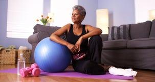 Ältere schwarze Frau, die auf Boden mit Übungsausrüstung sitzt Lizenzfreie Stockfotos
