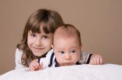 Ältere schwester die ihren babybruder umarmt lizenzfreie stockbilder
