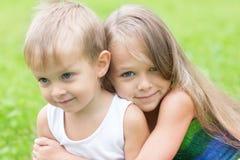 Ältere Schwester, die kleinen Bruder umarmt Lizenzfreie Stockbilder