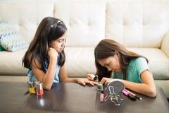 Ältere Schwester, die Nagelfarbe auf jüngeren Schwesternägeln anwendet lizenzfreies stockfoto
