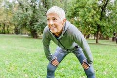 Ältere Sitz-Frau bereit zum Laufen in Natur lizenzfreie stockfotografie