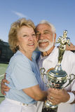 Ältere Tennis-Spieler mit der Trophäen-Umfassung Lizenzfreies Stockbild
